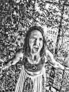 Screaming woman standing in front of vines