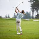 women mid stroke on golf course