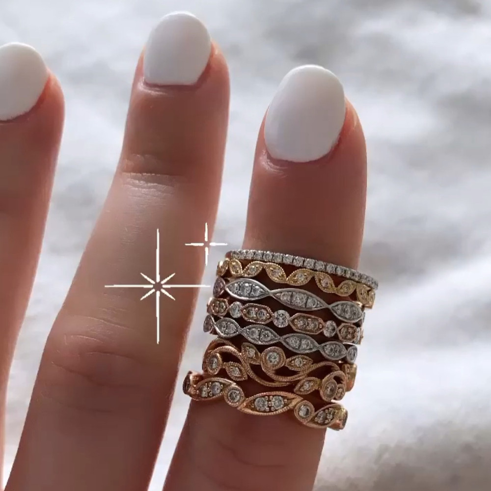 selection of vintage inspired diamond stacking bands ring stack of different colours rose white gold by Tsarina Gems worn on lady's hand with white nails on white background
