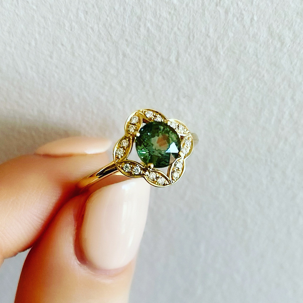 round green sapphire yellow gold vintage inspired clover diamond halo engagement ring cocktail ring by Tsarina Gems held in lady's hand neutral colour nails on white background
