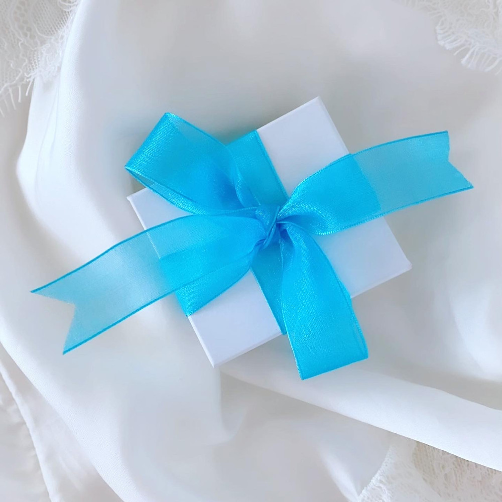 white ring box tied in a bow with blue ribbon on white silk background