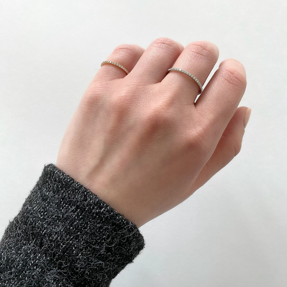 Selection of vintage inspired diamond stacking bands, pinkie ring,  in rose, white gold, by Tsarina Gems, on a lady's hand, grey sweater, on a white background