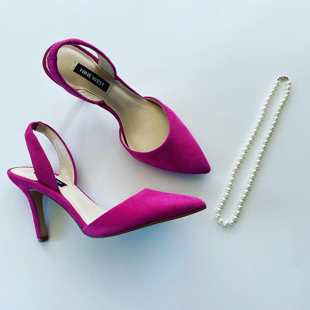 hot pink nine west shoes stilettos with pointed toe next to a pearl necklace lifestyle photography