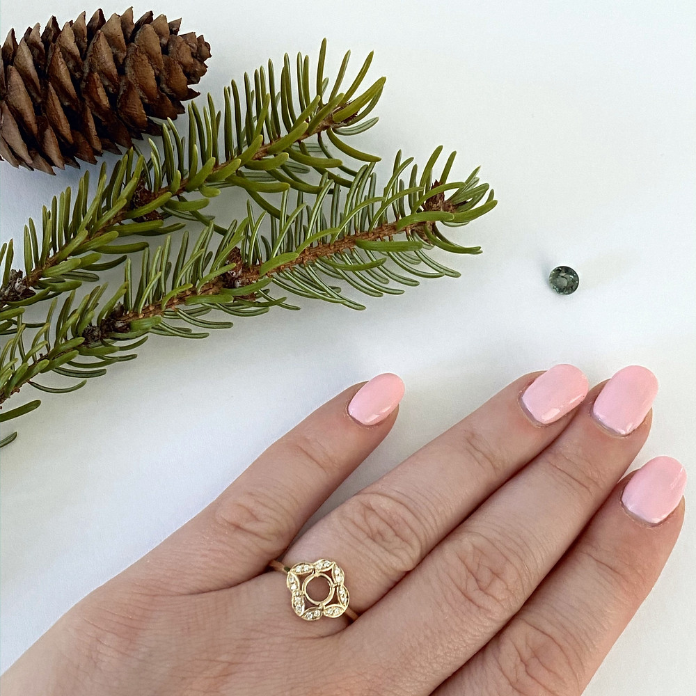 loose green sapphire ladies hand with pink nails wearing a yellow gold semi mount with diamonds pine cone fur tree branches on white background