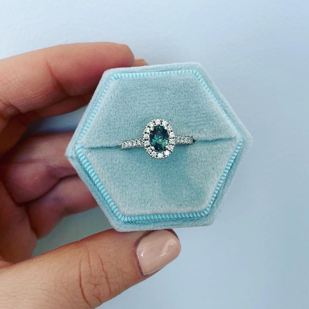 oval blue green teal sapphire and diamond halo white gold engagement ring in a blue velvet hexagonal ring box held in woman's hand