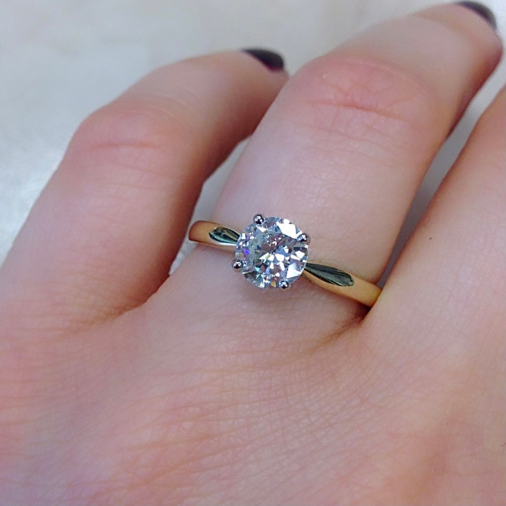 lady's hand wearing yellow gold diamond solitaire engagement ring