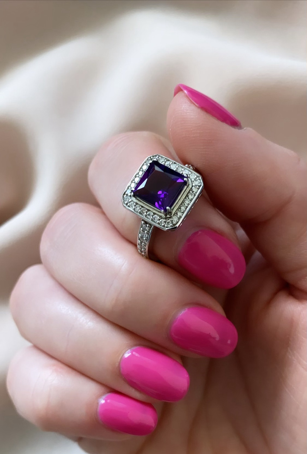 square dark purple amethyst in white gold diamond halo ring held in hand with hot pink nails on white silk background