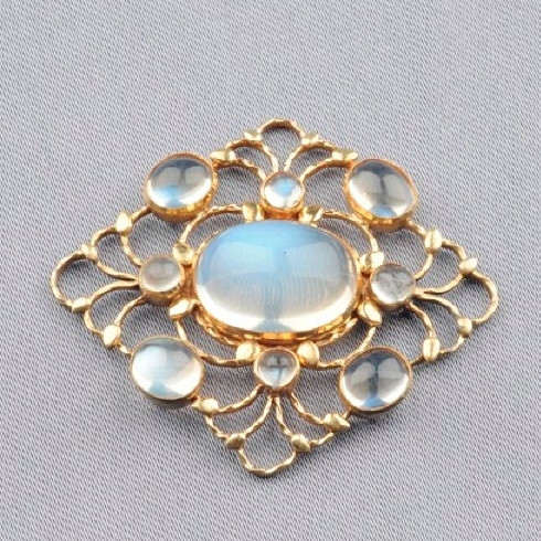 Art Nouveau inspired broach, yellow gold and 9 oval moonstone on a grey background