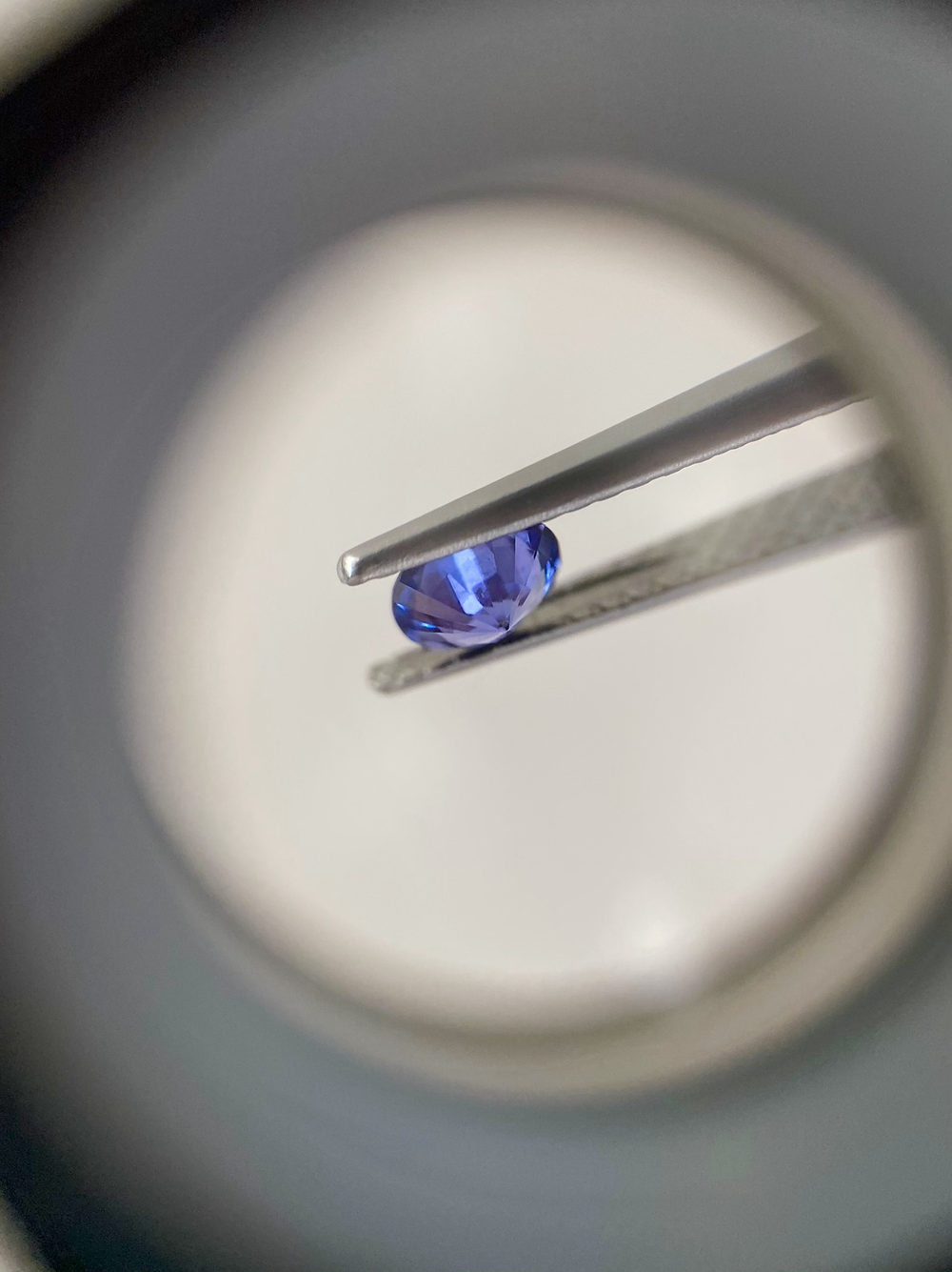 round purple sapphire held in tweezers under loupe magnification showing stone pavilion