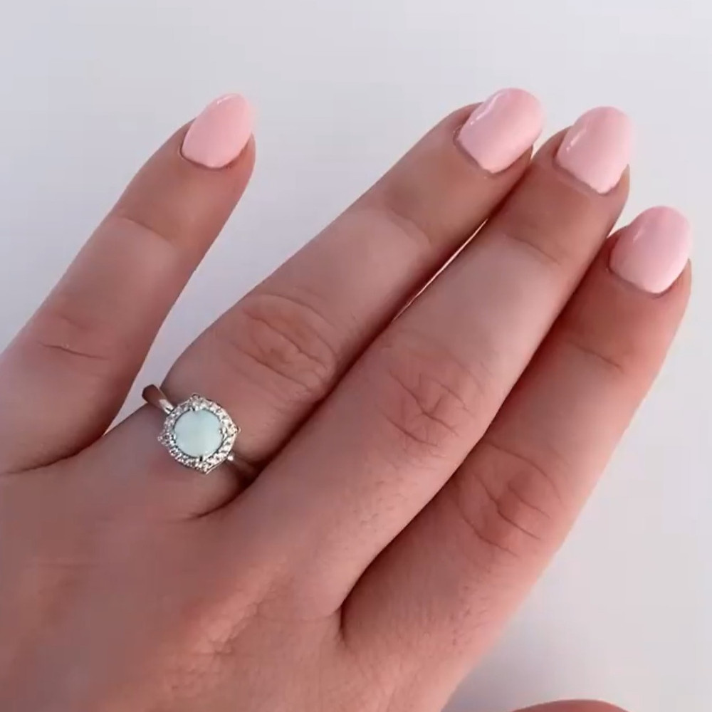 Woman's hand wearing a round opal and diamond halo white gold ring and pink nails