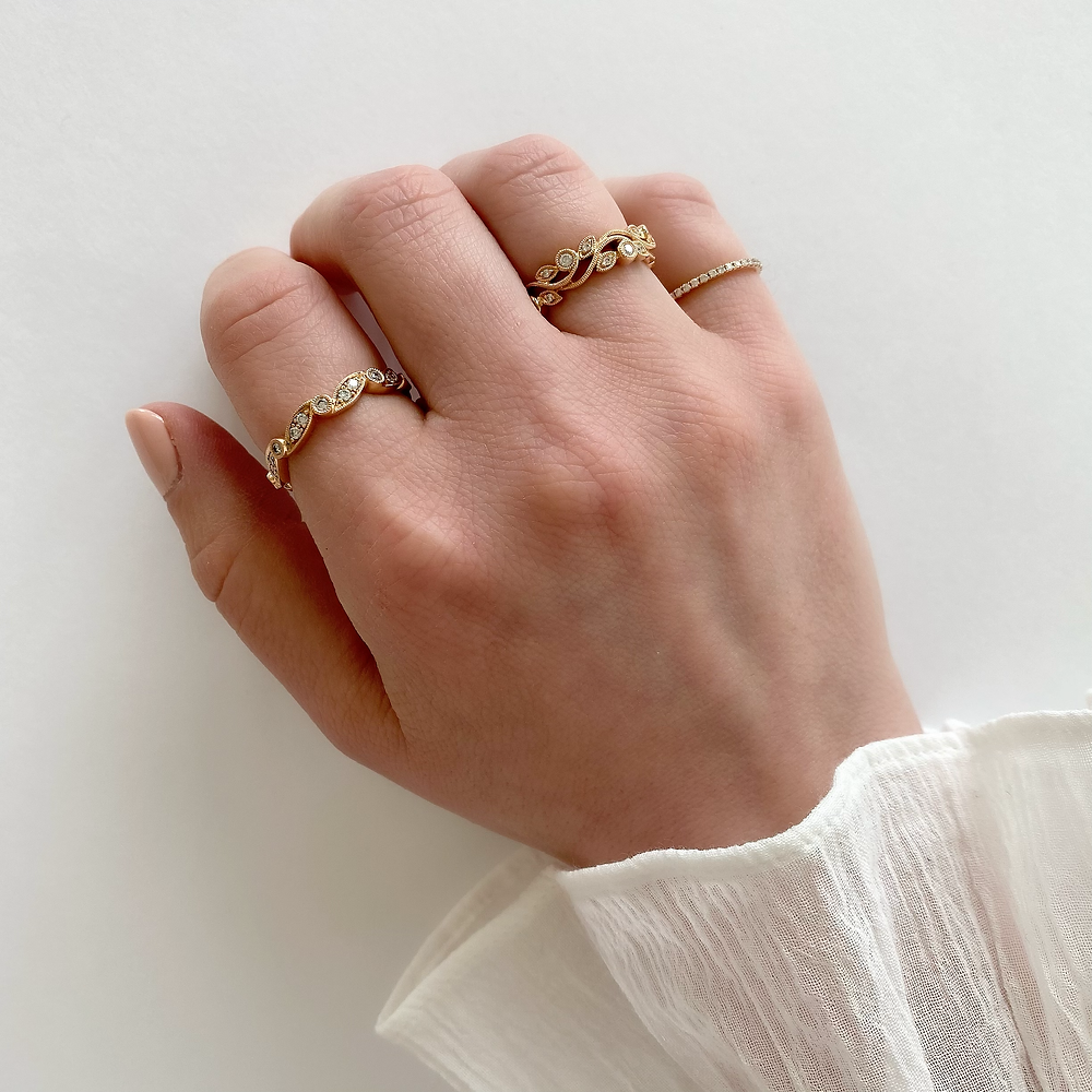 Lady's hand wearing a variety of vintage inspired, diamond stacking bands in rose gold