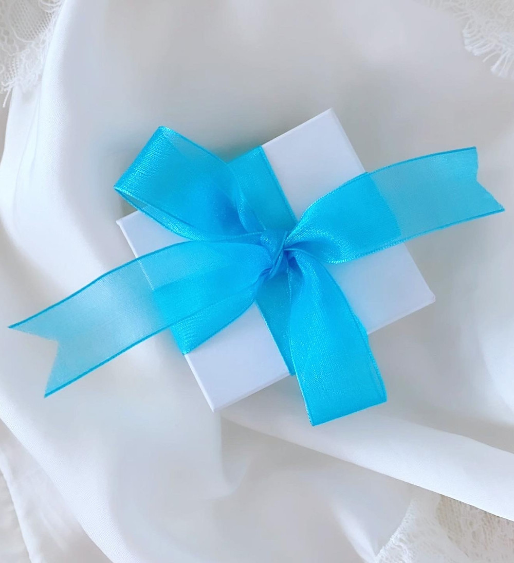 white gift box wrapped with a blue bow on a white silk background