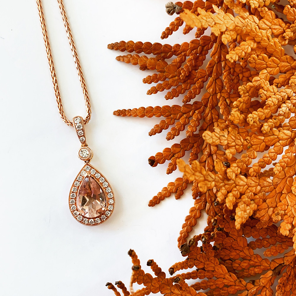 pear shape peach pink morganite pendant and wheat chain necklace in rose gold and diamond halo and bail on white background next to orange autumn colour dry leafs