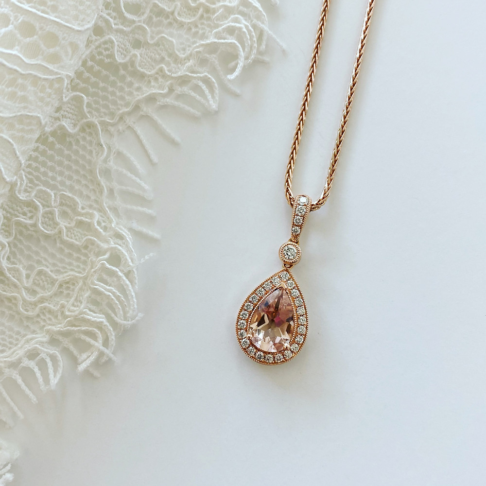 pear shape morganite and diamond halo rose gold pendant and chain on a white silk background