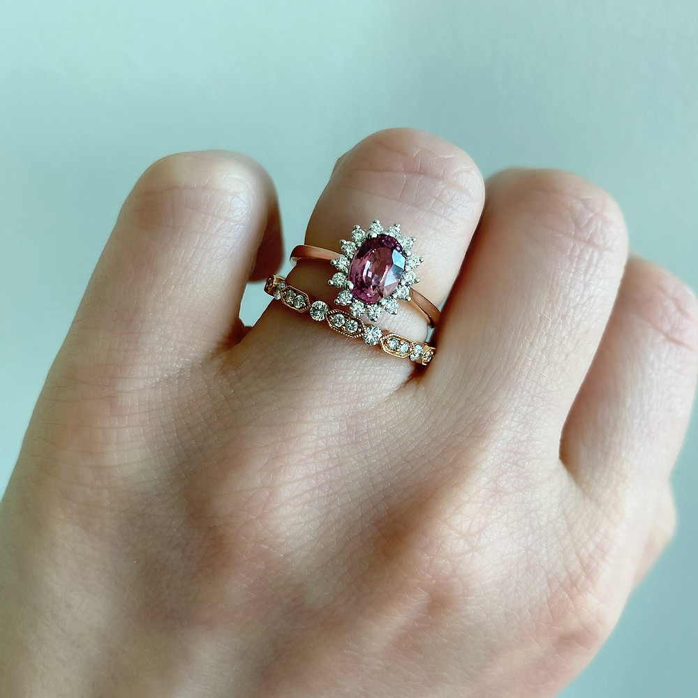 lady's hand wearing an oval padparadscha sapphire rose gold diamond halo vintage inspired engagement ring and diamond stacking ring, rose gold bridal set by Tsarina Gems