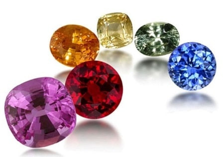 a variety of fancy coloured sapphires in different shades and shapes round cushion oval sapphires