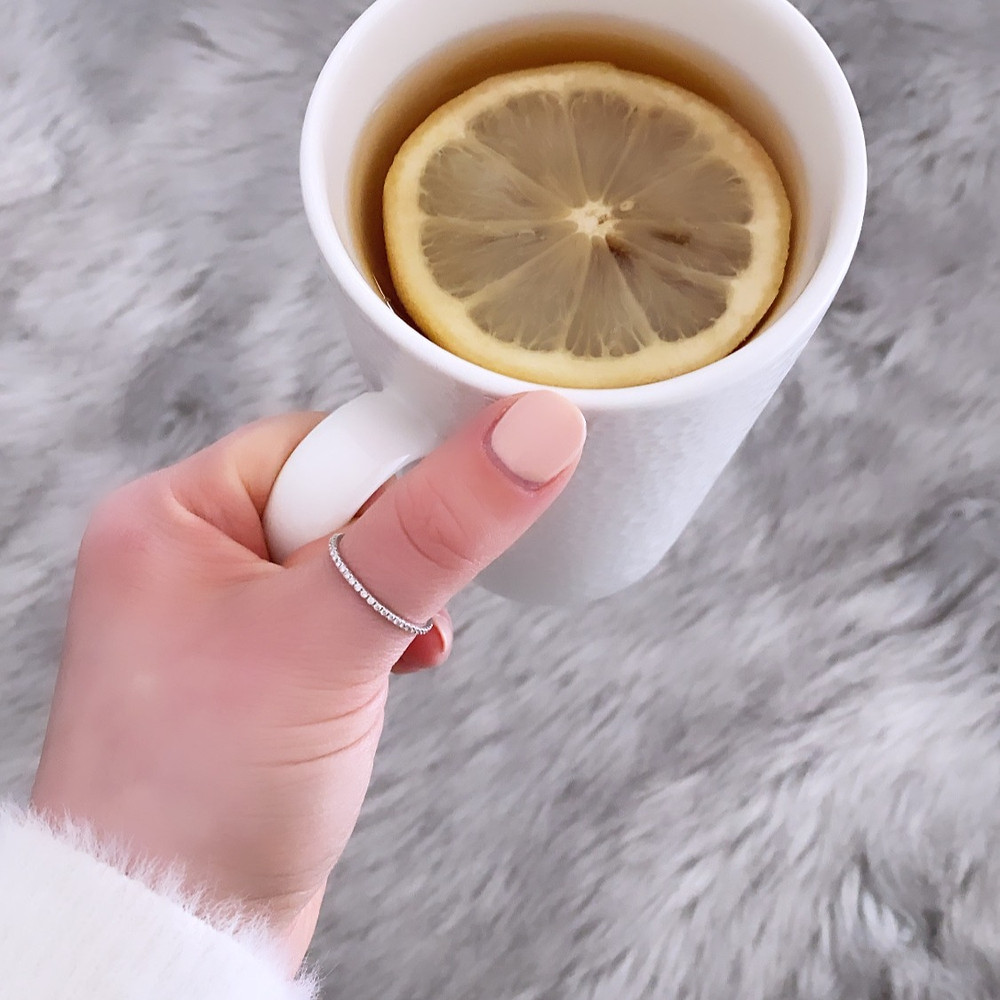 A lady's hand wearing a white gold diamond stacking ring by Tsarina Gems, with light pink nails, wearing a soft white sweater, holding a white mug with tea and a slice of lemon, against a grey faux fur blanket background