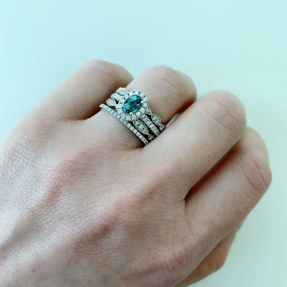 Lady's hand wearing an oval blue green teal sapphire white gold engagement ring and matching stacking rings on her ring finger