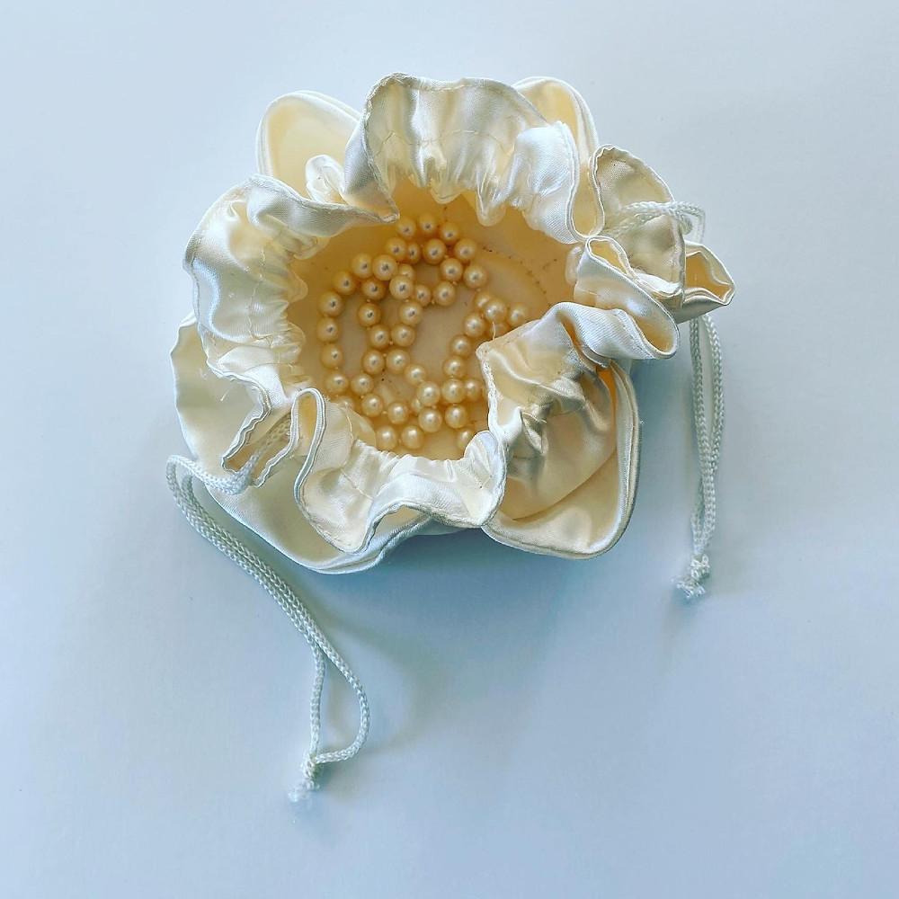 pearl necklace in an open beige silk pouch