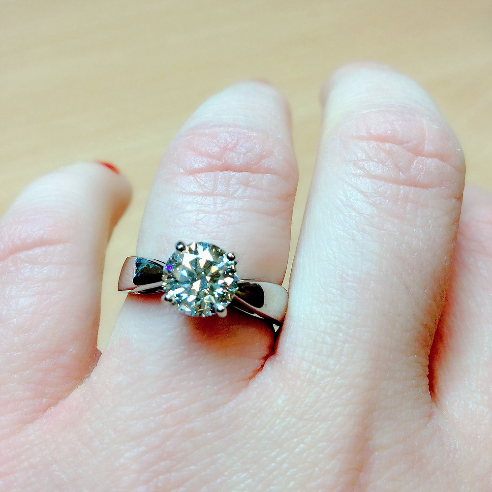 lady's hand wearing a large 2 carat solitaire diamond engagement ring,  thick white gold band