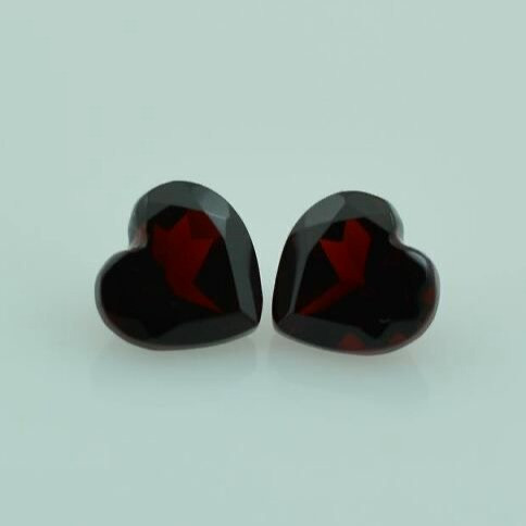 loose pair of dark red heart shape garnets on grey background