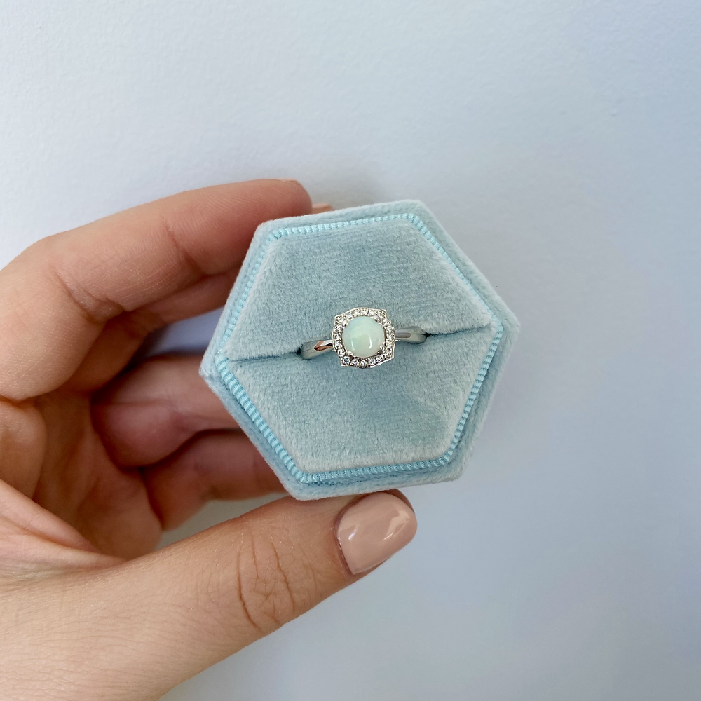lady's hand holding a hexagonal light blue ring box with a round opal and diamond halo white gold engagement ring inside