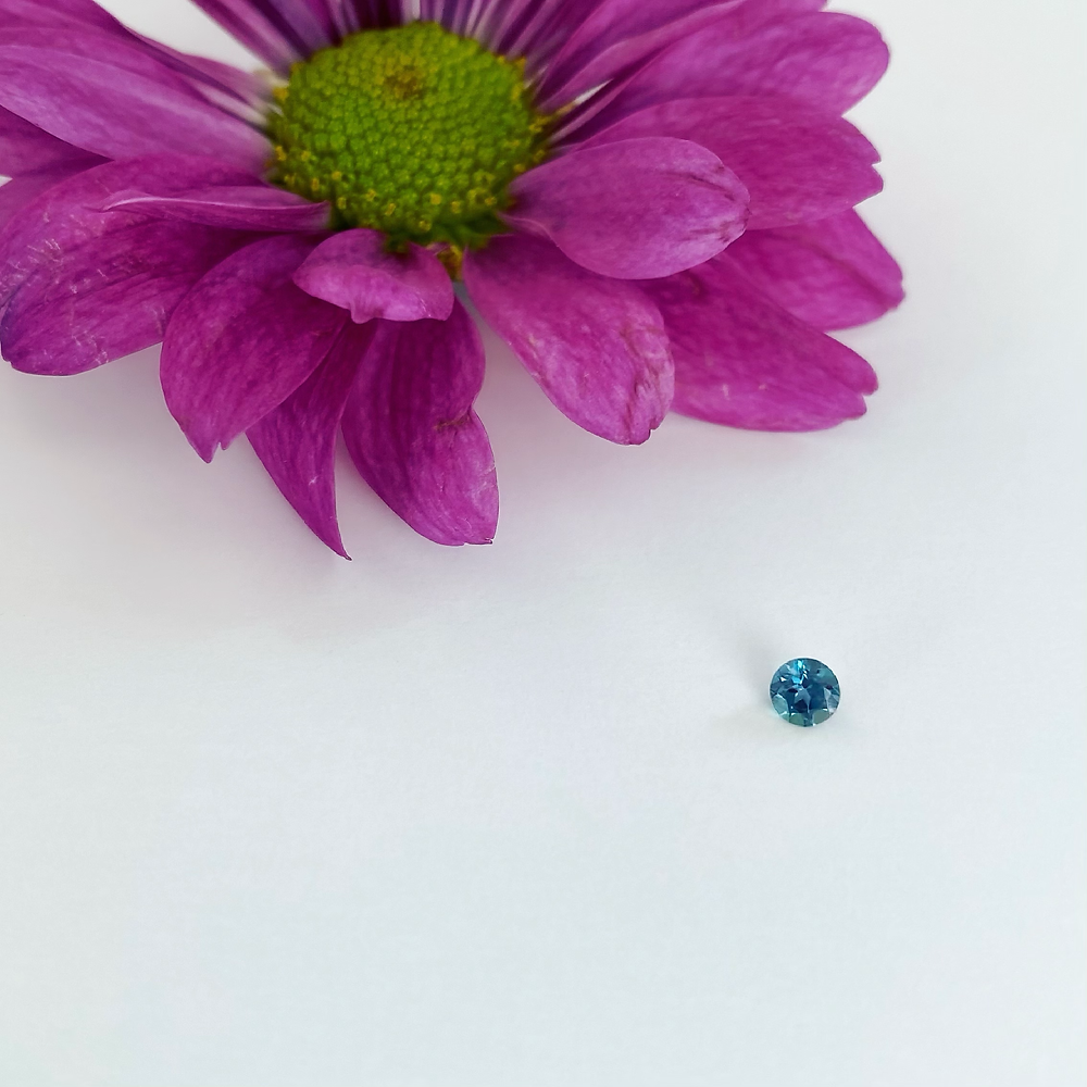 loose round alexandrite next to a pink flower on a white background