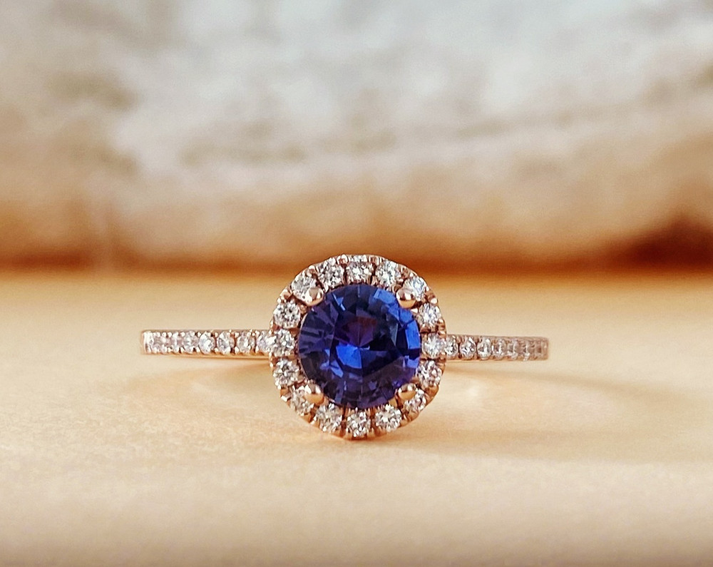 round purple sapphire rose gold diamond halo engagement ring cocktail ring by Tsarina Gems on a beige background