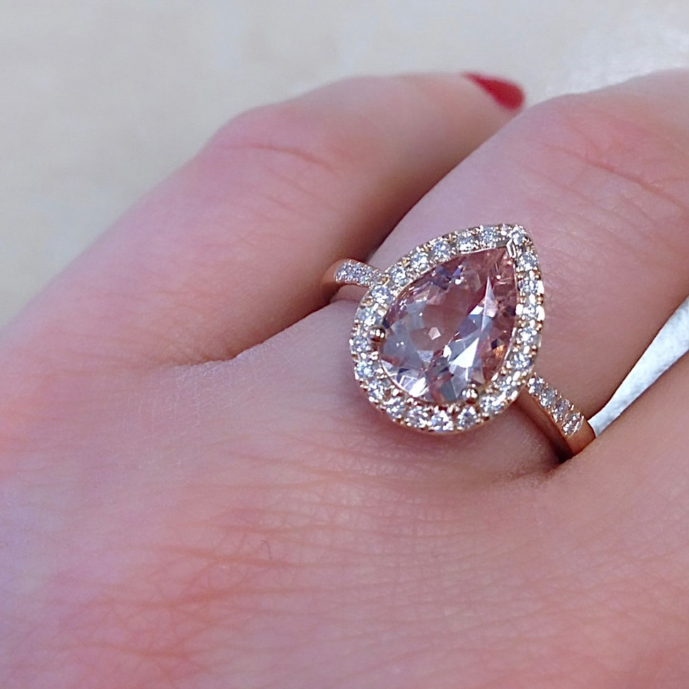 lady's hand wearing a large pear shape morganite, vintage inspired, diamond halo, rose gold, engagement ring, red nails
