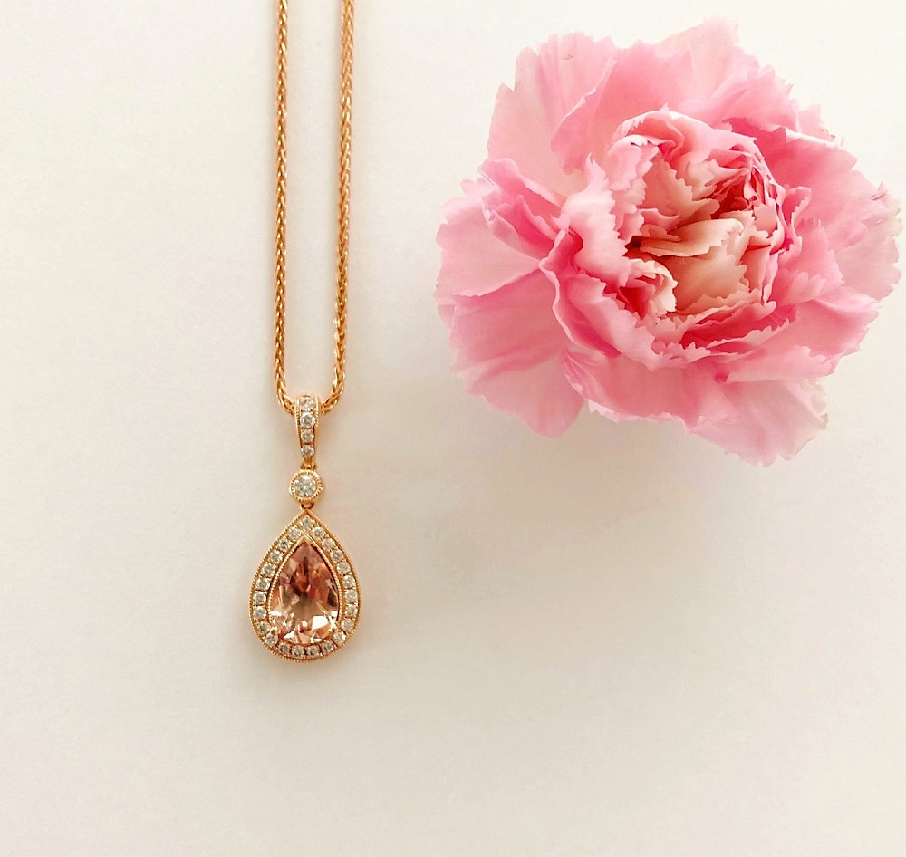 vintage inspired pear shape morganite and diamond halo rose gold pendant and chain by Tsarina Gems on a light background next to a pink carnation