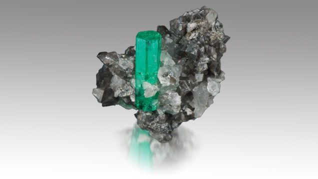 emerald rough crystal in a host rock on a grey background