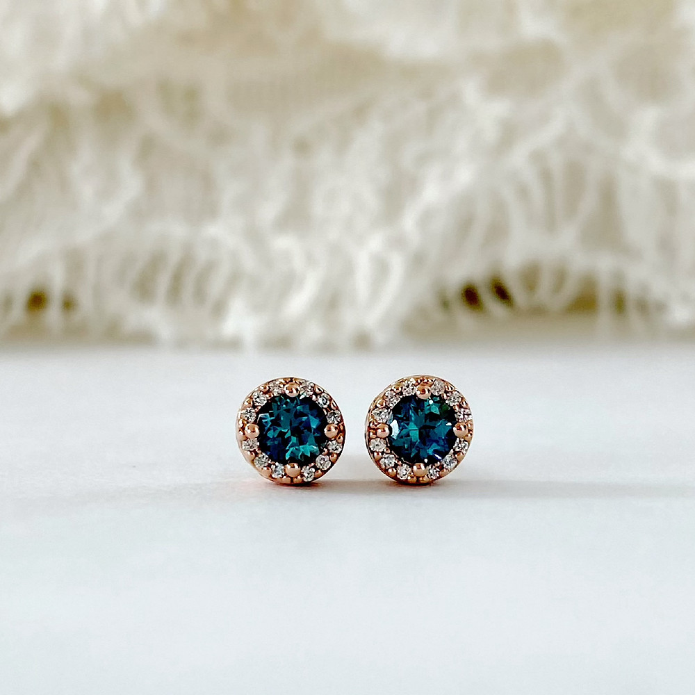 a pair or round alexandrite and diamond halo rose gold stud earrings on a silk background by Tsarina Gems