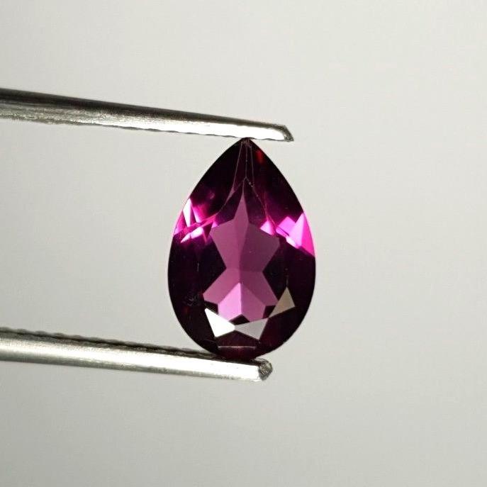 loose pear shape rhodolite, purple garnet held in tweezers on grey background
