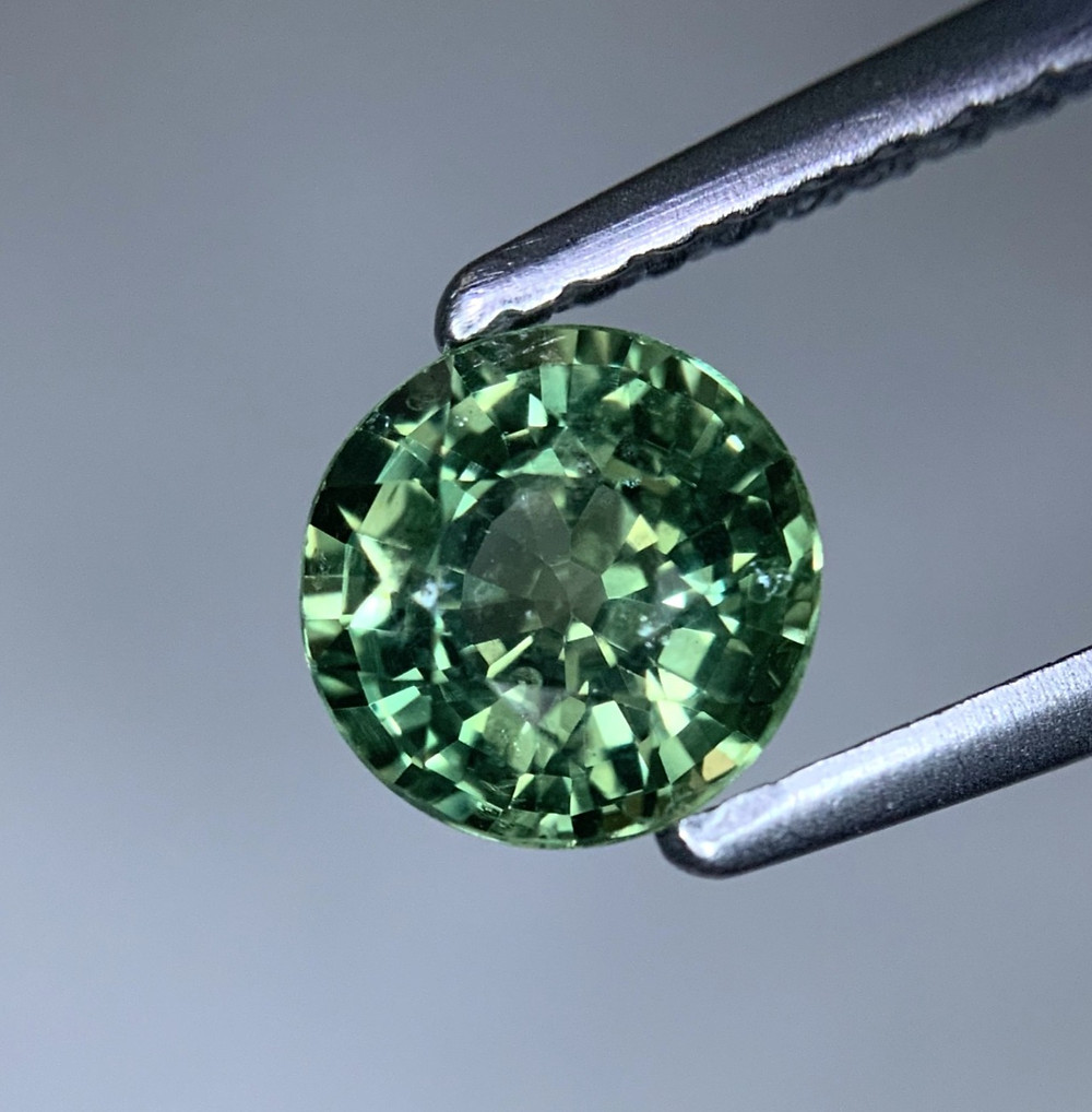 close up of loose round green sapphire held in tweezers under magnification viewed with a loupe showing inclusions crystals needles silk fingerprint on grey background