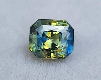 loose radiant cut bi colour, parti sapphire, blue and yellow sapphire, on a grey background