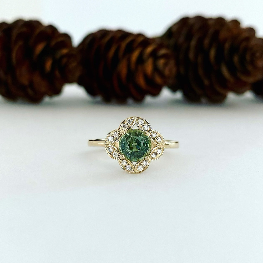 round blue green sapphire set in vintage inspired 14K yellow gold ring with diamonds by Tsarina Gems on white background and pine cones