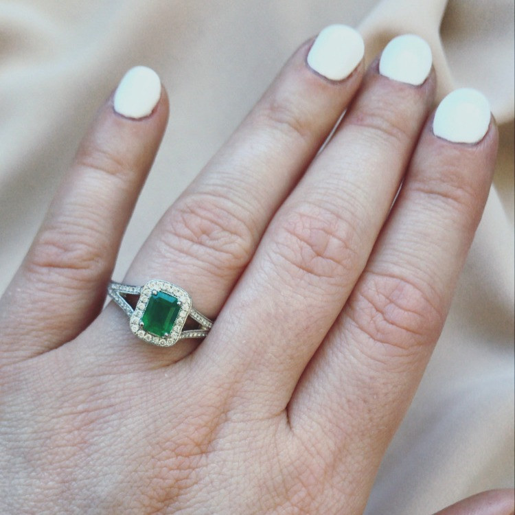lady's hand wearing an emerald cut emerald and diamond engagement ring cocktail ring vintage inspired white gold ring with split shank white nail polish on a beige background