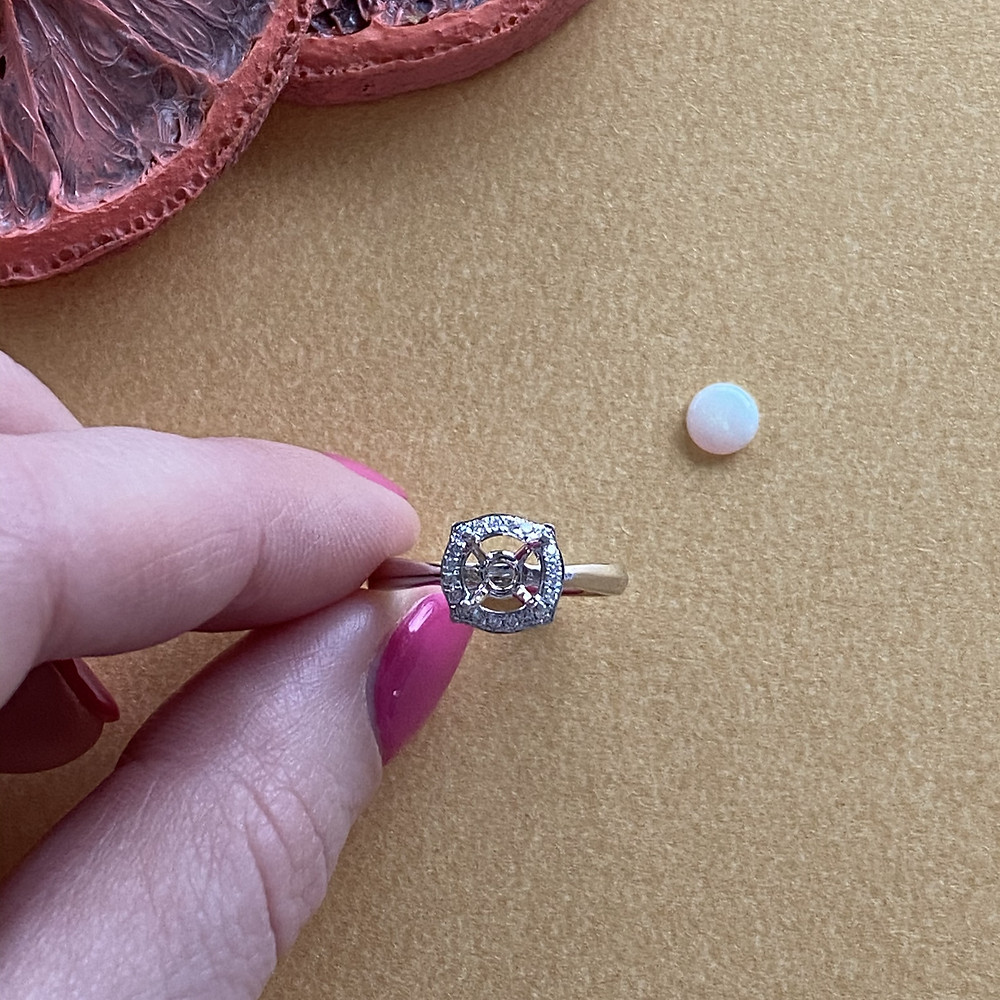 transparent translucent round white opal showing play of colour on gold background hand holding white gold diamond semi mount ring pink nails by Tsarina Gems