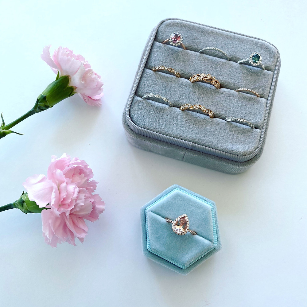 large multi-ring grey velvet ring box with a selection of vintage inspired engagement rings and stacking rings next to a small light blue velvet octagonal ring box with a vintage inspired pear shape morganite and diamond halo rose gold engagement ring by Tsarina Gems next to pink carnations on a light background