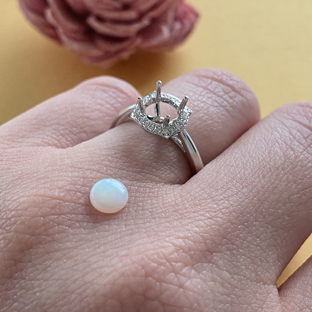 transparent translucent round white opal showing play of colour on hand wearing white gold diamond semi mount on gold background by Tsarina Gems