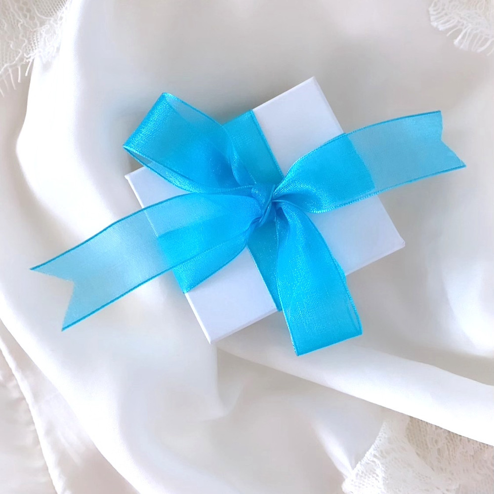 white jewellery box with a blue ribbon tied in a bow, by Tsarina Gems, on a white silk background