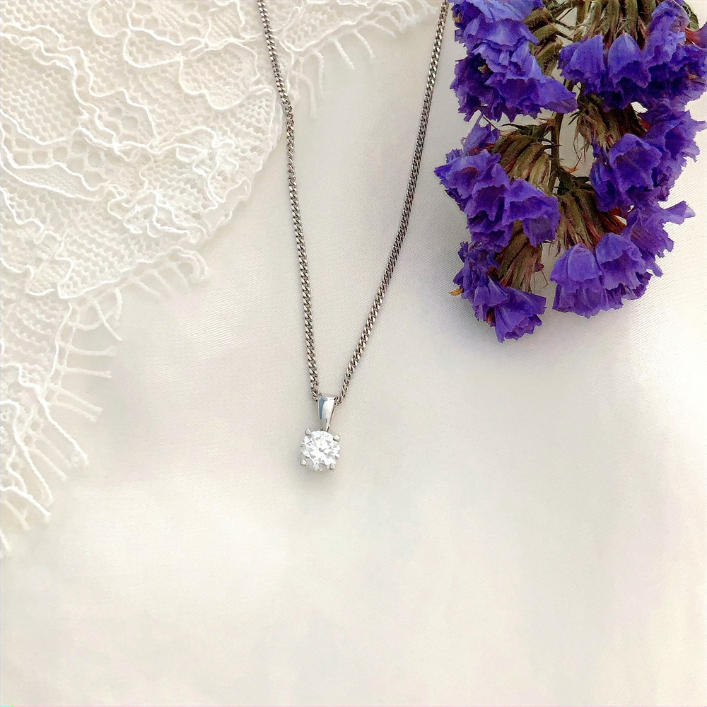 Round brilliant white gold diamond pendant on white lace background