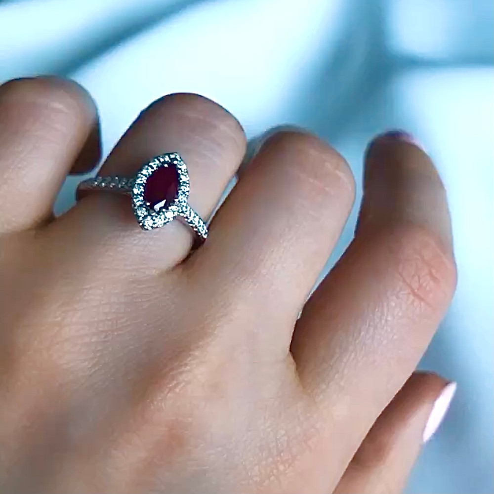 lady's hand wearing a vintage inspired marquise and diamond halo white gold engagement ring