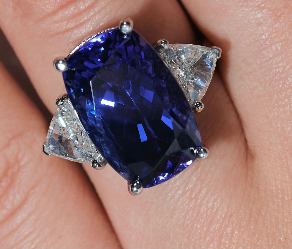 Woman's hand wearing a large cushion tanzanite and diamond cocktail ring