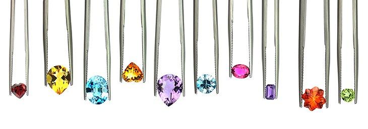 variety of multi-coloured gemstones held in a row in tweezers on white background