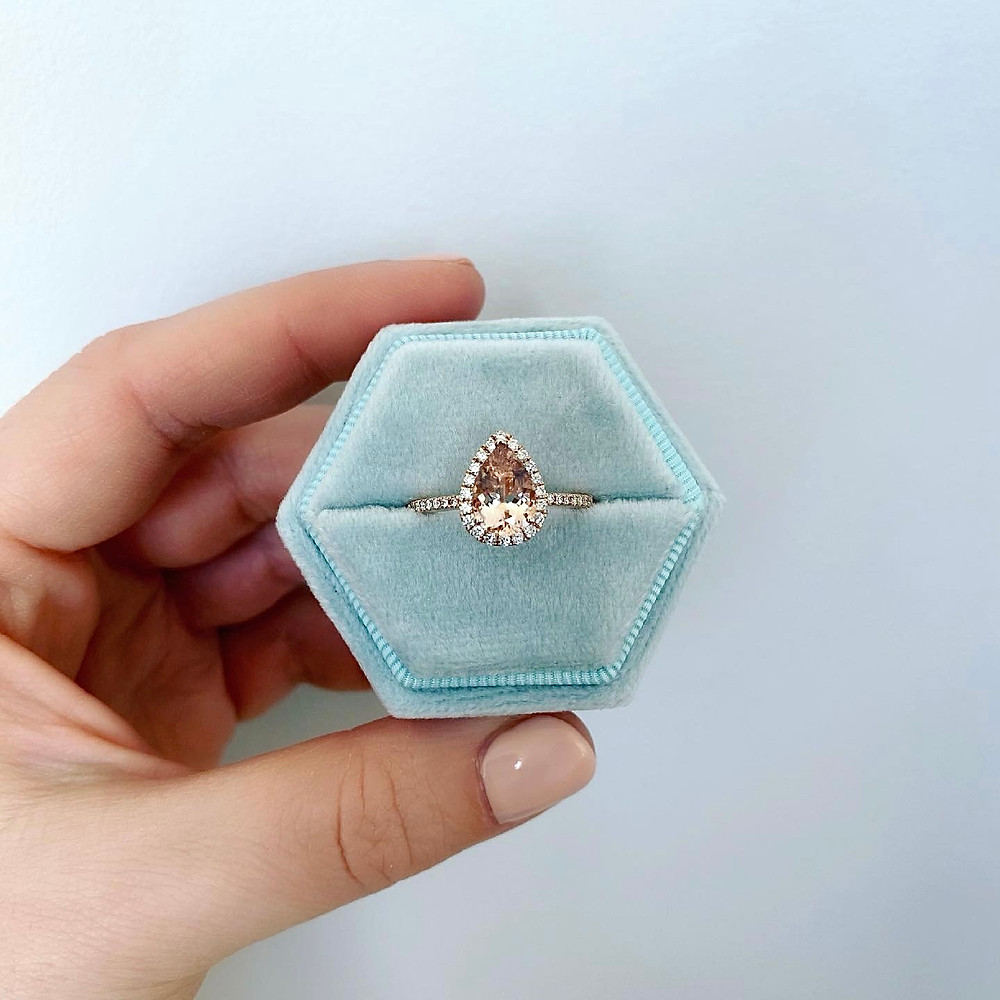 Woman's hand holding a light blue hexagonal ring box containing a pear shape morganite and diamond halo rose gold engagement ring