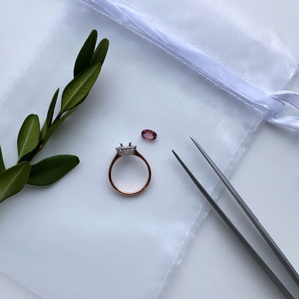 loose orangey pink oval Padparadscha sapphire next to two tone rose and white gold semi mount next to tweezers and evergreen on a white satin silk bag on a white background