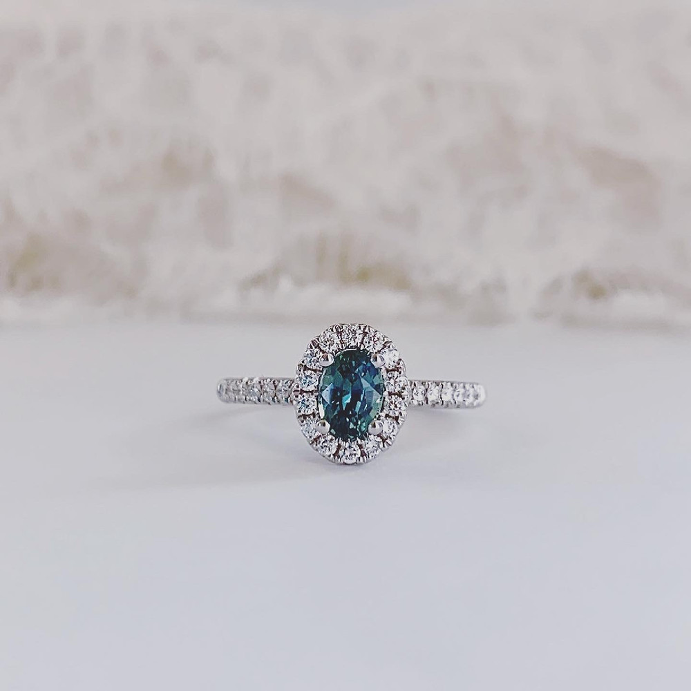 oval blue green sapphire and diamond halo white gold engagement ring, right hand ring, teal sapphire, mermaid sapphire, peacock sapphire, on a white background, by Tsarina Gems