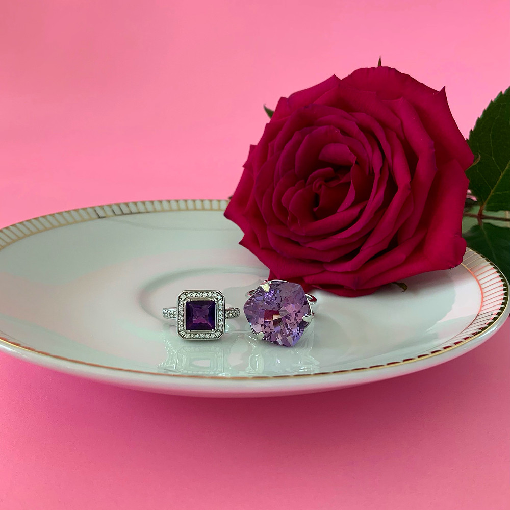 square dark purple amethyst in white gold diamond halo ring, large trilliant light amethyst white gold ring, on a small white plate with gold border, or hot pink background with hot pink red rose