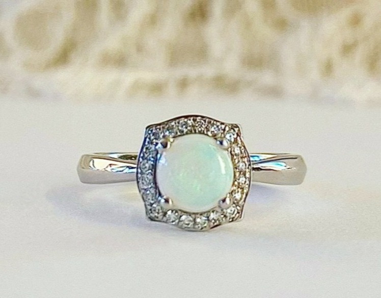 round white opal, natural diamond halo, vintage inspired white gold ring by Tsarina Gems, on a white and lace background